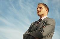 Man standing in front of blue sky, looking confident