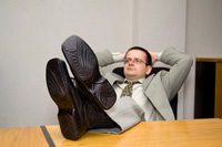 Overconfident negotiator leaning back in chair with feet on table - Peter barron stark companies