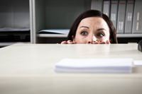 Scared woman hiding in office