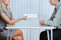 Man and woman sitting at desk and passing an envelope between them